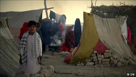 Child in front of tents at a camp near Mazar-i-Sharif as adults cook in the background