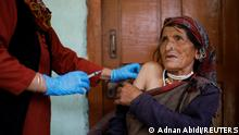 Kamla Devi, 58, a health worker, gives a dose of the COVISHIELD vaccine to a villager, as part of a vaccination drive during the coronavirus disease (COVID-19) outbreak, at Malana village in Kullu district in the Himalayan state of Himachal Pradesh, India, September 14, 2021. People were initially scared to take the vaccine, worried they would fall sick or die said village head Rajuram. Then I took it and others also mustered the courage. REUTERS/Adnan Abidi SEARCH REMOTE VILLAGERS VACCINE FOR THIS STORY. SEARCH WIDER IMAGE FOR ALL STORIES. TPX IMAGES OF THE DAY