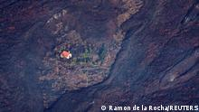 23/09/2021*** Lava flows surrounded a house following the eruption of a volcano in the Cumbre Vieja national park at El Paso, on the Canary Island of La Palma, Spain September 23, 2021. Ramon de la Rocha/Pool via REUTERS