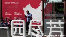 A security guard walks by a map showing Evergrande development projects in China at an Evergrande new housing development in Beijing, Wednesday, Sept. 22, 2021. The Chinese real estate developer whose struggle to avoid defaulting on billions of dollars of debt has rattled global markets announced Wednesday it will make a closely watched interest payment due this week, while the government was silent on whether it might intervene. (AP Photo/Andy Wong)