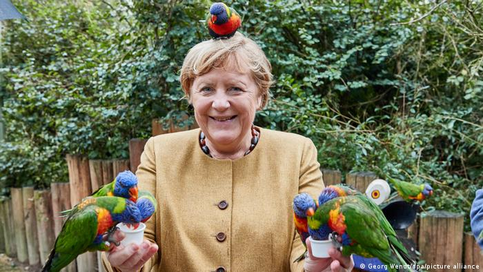 German Chancellor Angela Merkel poses with birds at the Vogelpark Marlow