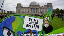An activist holds a banner saying Save the Climate, during a Fridays for Future global climate strike in Berlin, Germany, Friday, Sept. 24, 2021. (AP Photo/Markus Schreiber)
