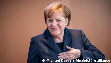 Bundeskanzlerin Angela Merkel (CDU), begrüßt die Umstehenden zu Beginn der wöchentlichen Sitzung des Bundeskabinetts im Kanzleramt mit einem Druck ihrer Hand auf die Brust. +++ dpa-Bildfunk +++