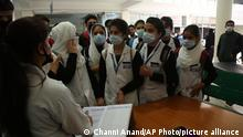 Indian medical students wear masks and gather for attendance at a medical college