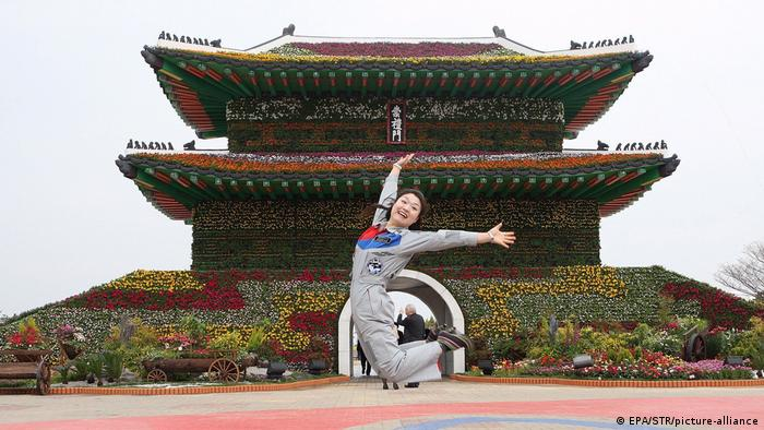 Yi So-yeon, South Korea astronaut, leaps and grins while wearing her official jumpsuit