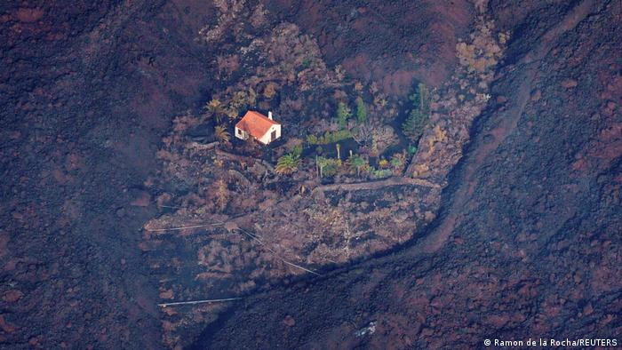 Luftaufnahme von einem Haus, links und rechts davon fließen Lavaströme, die die umliegenden Häuser mitgerissen haben.
