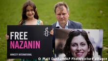 Richard Ratcliffe, the husband of imprisoned British-Iranian Nazanin Zaghari-Ratcliffe and their seven year old daughter Gabriella pose for the media backdropped by the scaffolded Houses of Parliament and the Elizabeth Tower, known as Big Ben