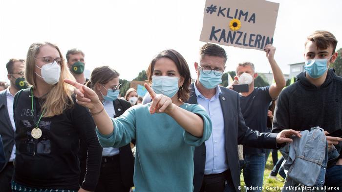 Annalena sinaliza com as mãos. Ela está ao ar livre e em meio a outras pessoas. Usa máscara, Atrás há um cartaz, com um girassol, símbolo dos verdes.