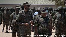 Rwanda President Paul Kagame (L) and Mozambican President Filipe Nyusi (R) both wearing military fatigue, review troops on 24 september 2021 in Pemba, Cabo Delgado province, Mozambique. - Close to 1,000 members of the Rwanda Defence Forces and Rwanda National Police are in the country working with the Mozambican Armed Defence Forces (FADM) and forces from the Southern African Development Community (SADC). The Rwandan joint forces are deployed in Cabo Delgado Province in northeastern Mozambique, where in collaboration with Mozambican Armed Defence Forces (FADM), they succeeded in liberating several key towns from terrorist groups. The towns liberated include the terrorist former stronghold of Mocimboa de Praia among others. (Photo by Simon WOHLFAHRT / AFP) (Photo by SIMON WOHLFAHRT/AFP via Getty Images)