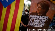 A mossos d'esquadra police officer stands behind a banner and a Catalonia independence flag with the image of former Catalan leader Carles Puigdemont with the message 'Puigdemont , Our leader' as people take part in a protest outside the Italian consulate in support of Puigdemont in Barcelona, Spain, Friday, Sept. 24, 2021. Puigdemont, who fled Spain after a failed secession bid for the northeastern region in 2017, was detained Thursday in Sardinia, Italy, his lawyer said. Puigdemont, who lives in Belgium and now holds a seat in the European Parliament, has been fighting extradition to Spain, which accused him and other Catalan independence leaders of sedition. (AP Photo/Joan Mateu)