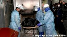 In this photo provided by Peru's Interior Ministry, crematorium workers place the body of Abimael Guzman, founder and leader of the Shining Path guerrilla movement, into an oven in Callao, Peru, Friday, Sept. 24, 2021. The Peruvian government cremated Guzman on Friday, according authorities. (Rolly Reyna/Peruvian Interior Ministry via AP)
