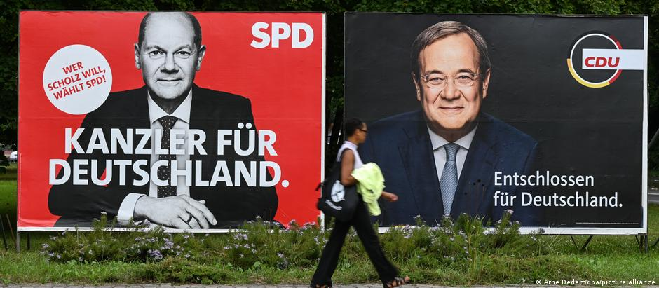 A woman walking past campaign posters for Scholz and Laschet in Frankfurt am Main