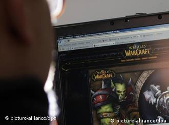 A man faces a computer monitor displaying content from the computer game World of Warcraft