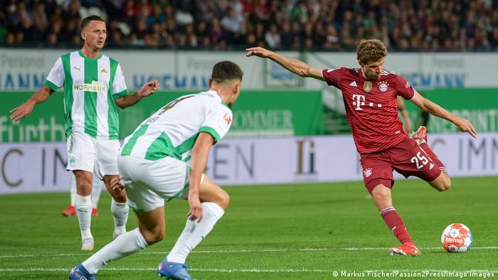 Thomas Müller kicks a soccer ball with a defender in the foreground