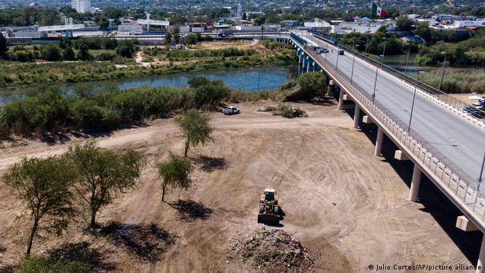 Foto mostra um terreno vazio. Há uma patrola sobre o terreno.