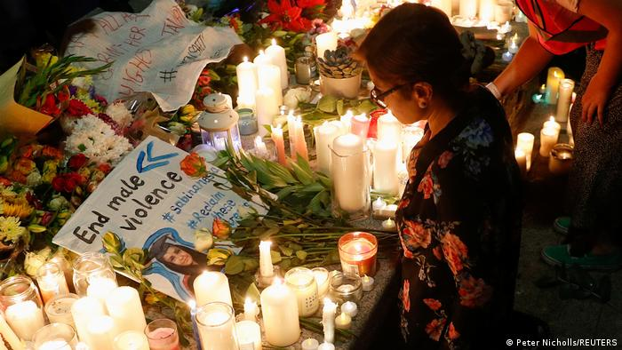 A placard is seen among flowers and candles during a vigil in memory of Sabina Nessa, a teacher who was murdered in a London park