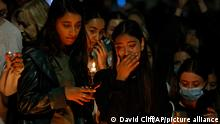 A woman is pictured crying at a vigil honoring murdered teacher Sabina Nessa in London