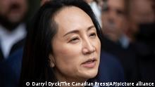 Meng Wanzhou, chief financial officer of Huawei, reads a statement outside B.C. Supreme Court in Vancouver, British Columbia, Friday, Sept. 24, 2021. (Darryl Dyck/The Canadian Press via AP)