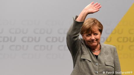 Angela Merkel waves before a banner of the CDU