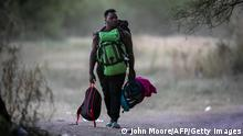 CIUDAD ACUNA, MEXICO - SEPTEMBER 23: A Haitian immigrant walks to the bank of the Rio Grande to cross into Del Rio, Texas on September 23, 2021 in Ciudad Acuna, Mexico. On the U.S. side of the border up to 14,000 immigrants had been encamped in squalid conditions. U.S. immigration officials say they have mostly cleared the camp of immigrants, deporting some and releasing others to pursue asylum claims in the United States. John Moore/Getty Images/AFP (Photo by JOHN MOORE / GETTY IMAGES NORTH AMERICA / Getty Images via AFP)