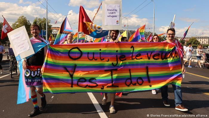 Protesters carry a rainbow flag that reads, 'Yes, I do!'
