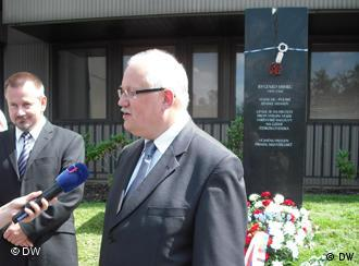 Polish ambassador Jan Pastwa in front of monument