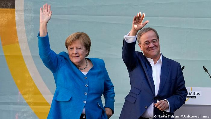 Chancellor Angela Merkel and Governor Armin Laschet wave to supporters at a campaign event in Aachen