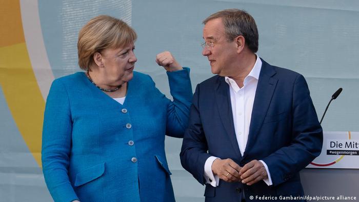 Merkel faz sinal de força com o braço enquanto olha para Laschet.