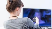 woman uses the remote to watch TV