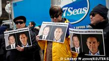 FILE PHOTO: People hold placards calling for China to release Canadian detainees Michael Spavor and Michael Kovrig outside a court hearing for Huawei Technologies Chief Financial Officer Meng Wanzhou at the B.C. Supreme Court in Vancouver, British Columbia, Canada, March 6, 2019. REUTERS/Lindsey Wasson/File Photo
