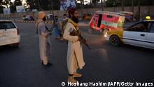 Taliban fighters stand guard along a road in Herat on September 21, 2021. (Photo by Hoshang Hashimi / AFP) (Photo by HOSHANG HASHIMI/AFP via Getty Images)