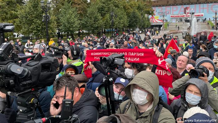 some people hold up a red scarf with Russian text on it in a crowd of people and camera operators
