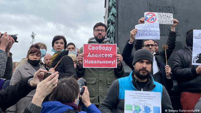 protesters stands with placards calling for the release of Alexei Navalny