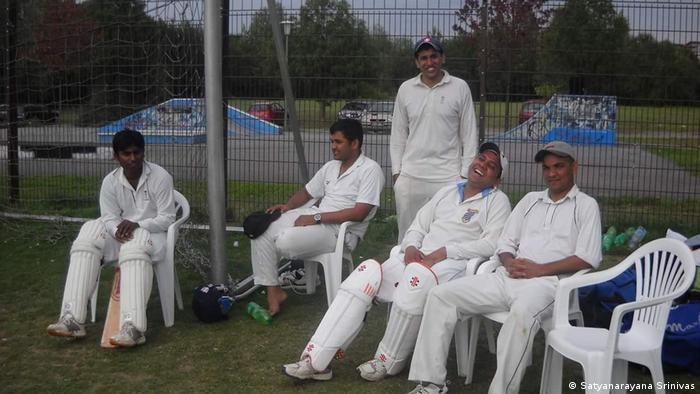 A group of men sit in plastic chairs at the sidelines of a cricket game in Bochum