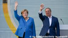 25/09/2021*** Christian Democratic Union CDU leader and chancellor candidate Armin Laschet (R) and German Chancellor Angela Merkel stand on stage as they wave to supporters during their campaign rally in Aachen, western Germany, on September 25, 2021, one day ahead of the German federal elections. (Photo by Ina Fassbender / AFP) (Photo by INA FASSBENDER/AFP via Getty Images)