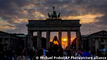 Tourists take pictures as the sun sets behind the Brandenburg Gate in Berlin, Germany, Saturday, Sept. 25, 2021. (AP Photo/Michael Probst)