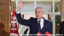 Tunisian President Kais Saied waves to Tunisian citizens as he delivers a speech during his visit to Sidi Bouzid, Tunisia, Monday, Sept. 20, 2021. Tunisia's president has announced plans to draft a new electoral code and appoint a transitional leadership and to hang on to the exceptional powers that he seized in July, throwing the country's young democracy into question. (Slim Abid/Tunisian Presidency via AP)
