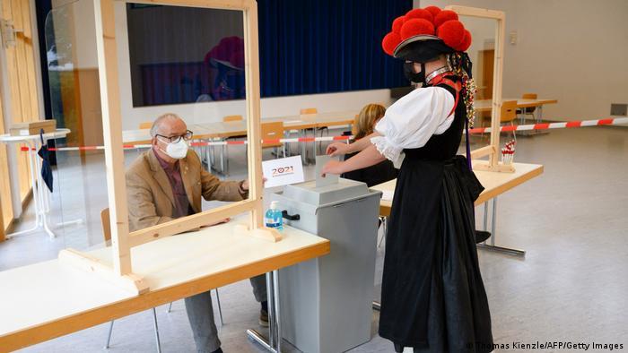 ۶۰ میلیون و ۴۰۰ هزار نفر از شهروندان واجد شرایط به پای صندوقهای رای فرا خوانده شدند تا دولت جدید آلمان را تعیین کنند. تمهیدات ضد کرونایی در حوزههای اخذ رای مشهود بود. ۳۱ میلیون و ۲۰۰ هزار نفر از رایدهندگان را زنان تشکیل میدهند. (این عکس زنی با لباس سنتی در کوتاخ در نزدیکی شهر فرایبورگ، واقع در ایالت بادن ووتنبرگ در پای صندوق رای را نشان میدهد)