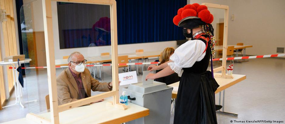 A woman wearing a traditional Bollenhut pompon hat typical for the Black Forest region casts her vote for the German federal elections at a polling station in Gutach near Freiburg