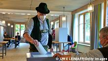 26/09/2021 A voter wearing traditional clothes of the region casts his ballot at a polling station during general elections in Bayrischzell, southern Germany, on September 26, 2021. (Photo by UWE LEIN / AFP) (Photo by UWE LEIN/AFP via Getty Images)