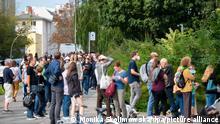 Em foto externa, diversos eleitores aguardam em fila para votar