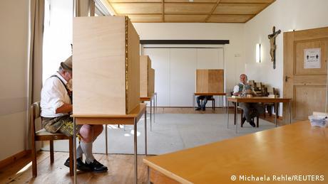 A German man wearing traditional Bavarian garb, including lederhosen, votes at a precinct in Benediktbeuern, Bavaria, on September 26
