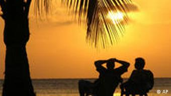 Люди на пляже смотрят закат