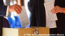Armin Laschet, left, Christian Union parties candidate for Chancellery and Minister President of North Rhine-Westphalia holds his ballot visible as he casts his vote with his wife Susanne, at a polling station for the German parliament election in Aachen, Germany, Sunday, Sept. 26, 2021. On Sept. 26, 2021 about 60.4 million people in the nation of 83 million are eligible to elect the new Bundestag, or lower house of parliament, which will elect the next head of government. (Thilo Schmuelgen/Pool via AP)