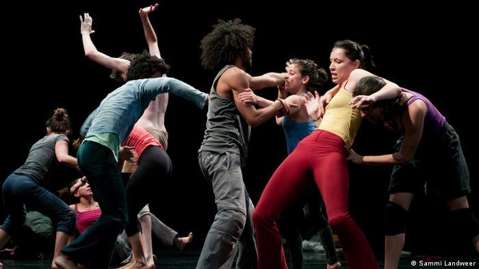 9 Tänzerinnen und Tänzer der Lia Rodrigues Companhia de Danças in bunten Kleidern scheinbar chaotisch ineinander verschlungen auf der Bühne