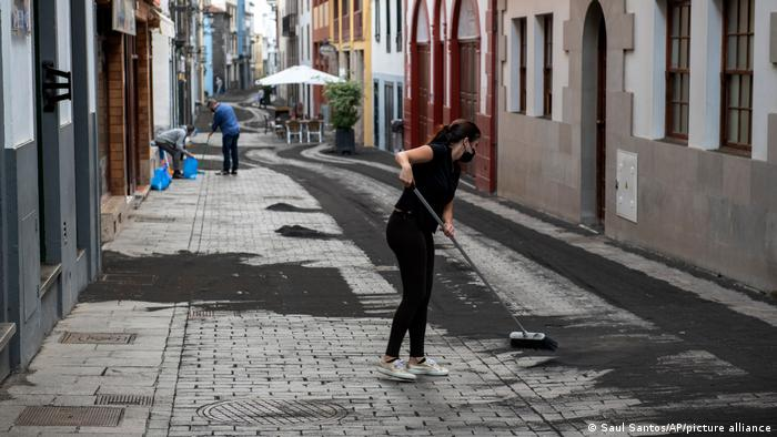 La Palma residents clean the ash from the streets with brooms