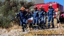 Firefighters carry the body of a man, retrieved from the rubble of a demolished church following an earthquake, in the town of Arkalochori on the island of Crete, Greece, September 27, 2021. REUTERS/Stefanos Rapanis