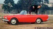 Mit einem sportlichen Sprung über die Fahrertür verläßt ein junger Mann einen roten Sunbeam Alpine 260 Tiger, der während der Frankfurter Automobilausstellung 1965 vorgestellt wird. Das sportliche Cabriolet verfügt über einen 4267 ccm Hubraum, 141 PS und eine Spitzengeschwindigkeit von 190 Stundenkilometern. Sein Preis beträgt rund 17 000 Mark.
