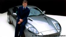 Lächelnd lehnt der irische Schauspieler Pierce Brosnan an einem Aston Martin V12 Vanquish bei einem Pressetermin am 11.1.2002 in den Pinewood Studios in London. Der 600000 Mark teure Sportwagen, der eine Spitzengschwindigkeit von 320 Kilometern in der Stunde erreicht, wird künftig der neue Dienstwagen von James Bond alias Pierce Brosnan sein. Zu Beginn der Dreharbeiten zu einem neuen James-Bond-Film, für den es noch keinen Titel gibt, ist der Hauptdarsteller Pierce Brosnan Spekulationen über ein baldiges Ende seiner Karriere als Geheimagent 007 entgegen getreten. Der Film, dessen Dreharbeiten jetzt beginnen, ist Brosnans vierter als James Bond.