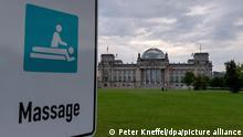 """Ein Schild mit der Aufschrift """"Massage"""", das noch vom vergangenen Stadtmarathon stehen geblieben ist, steht vor dem Reichstag."""